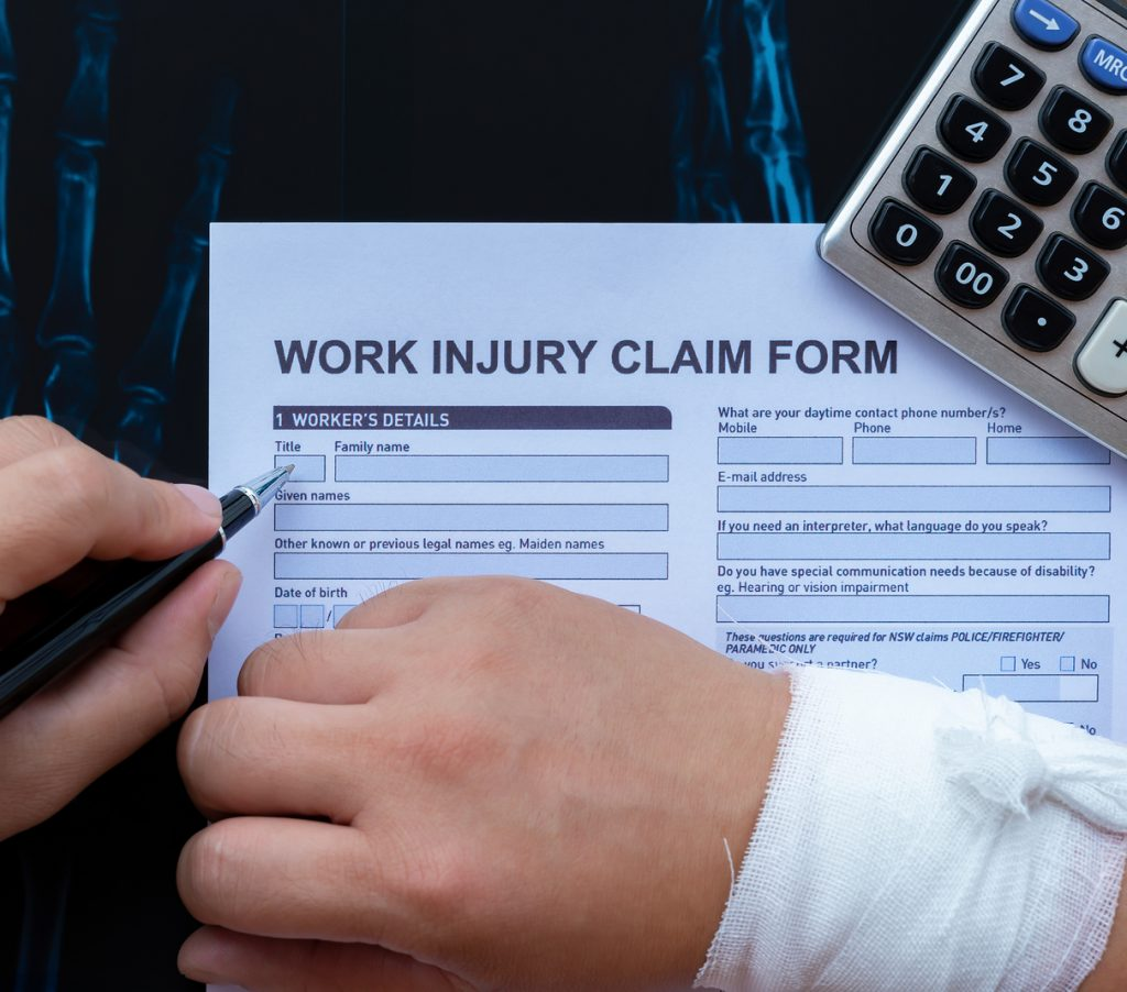 Filling Up A Work Injury Claim Form With A Wrapped Hand On Top O